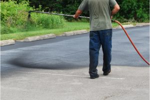 Asphalt Sealcoating by a worker with a sprayer