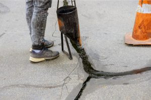 Driveway Crack Repair by a worker with sealcoating tool