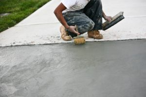 Paving Driveway by a worker with two brushes